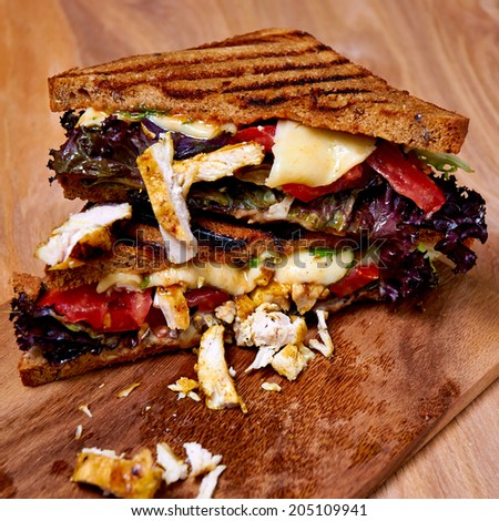 Chicken club sandwich on wooden board, mozzarella, tomatoes, roca-loca salad, lettuce - stock photo