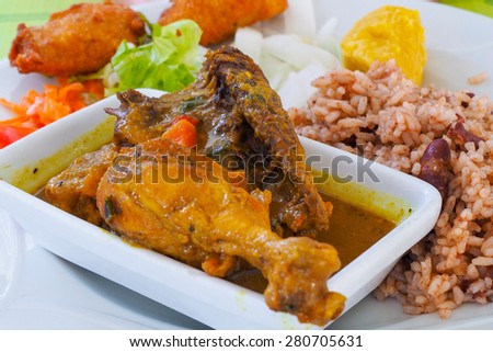 Chicken colombo, typical dish of the tradition in Guadeloupe, made with chicken legs and spices. Served with accras, appetizer made with fish. - stock photo
