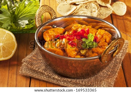 Chicken curry in a balti dish, with mini poppadums, salad and lemon. - stock photo