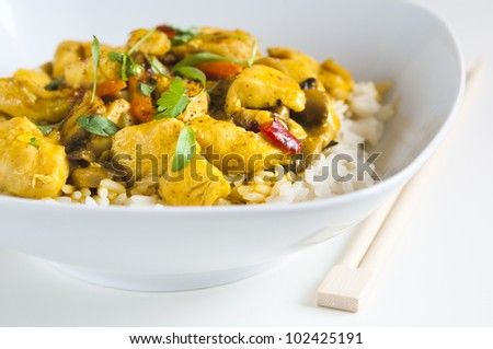 Chicken curry in a white bowl with chopsticks