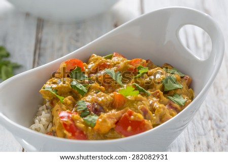 chicken curry, red pepper and coriander leaves with rice in a white bowl - stock photo