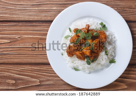 Chicken curry with rice and cilantro on a plate horizontal top view  - stock photo