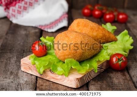 Chicken cutlets in breadcrumbs on Kiev (Chicken Kiev) on wood board and wooden background. Ukrainian cuisine. Selective focus - stock photo