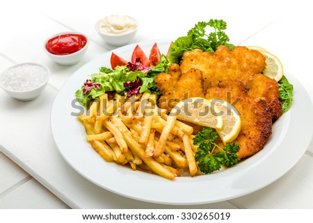 Chicken cutlets with french fries, ketchup, mayo, lemon and salad - stock photo