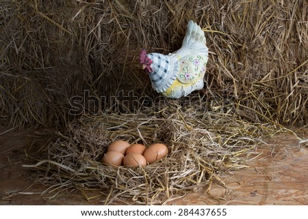 Chicken doll with cold eggs in the straw nest, still life style