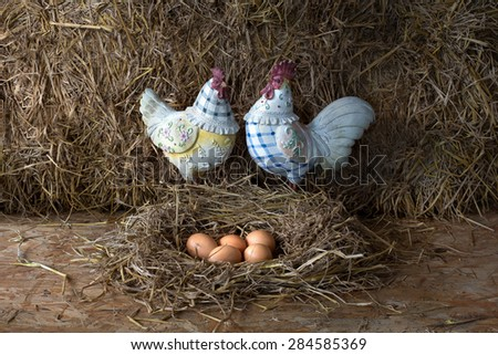 Chicken doll with eggs in the straw nest, still life style