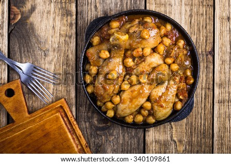 Chicken drumsticks curry with chickpeas in frying pan on wooden table, top view - stock photo