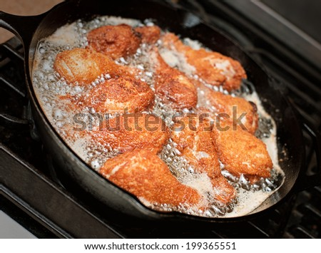 Chicken drumsticks frying in a pan