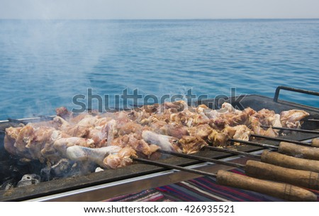 Chicken drumsticks on skewers cooking on BBQ barbecue with tropical ocean background - stock photo