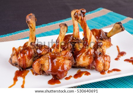 Chicken drumsticks served in BBQ sauce, a creative Spanish tapa