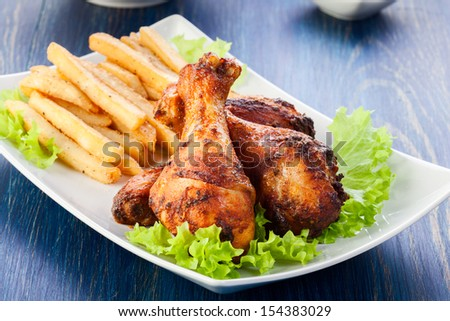 Chicken drumsticks with french fries. Selective focus  - stock photo