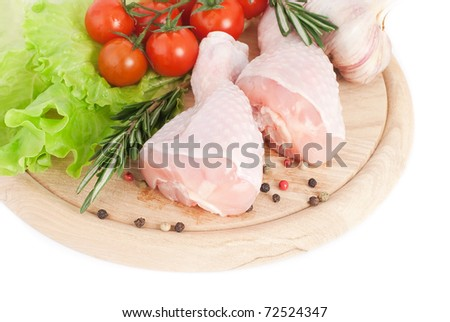 Chicken drumsticks with vegetables on the cutting board