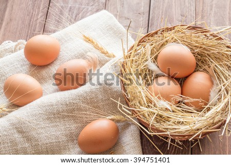 Chicken eggs in a basket with hay - stock photo
