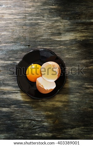 Chicken eggs in a bowl on old vintage wooden background. Ingredients for cooking. View from above. Rustic style. Toned image - stock photo