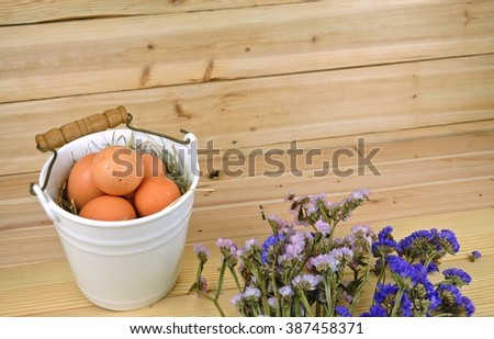 Chicken eggs in a ceramic basket decorate with pink and purple flower on the wooden table.Easter festival. - stock photo