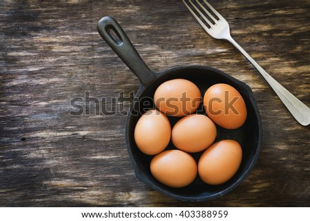Chicken eggs in a frying pan over a vintage old wooden table. Ingredients for cooking. Rustic style.  View from above. - stock photo