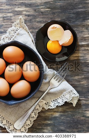 Chicken eggs in a frying pan over a vintage old wooden table. Ingredients for cooking. Rustic style.  View from above.  Toned image - stock photo