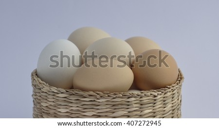 Chicken eggs in a wicker basket on a white background