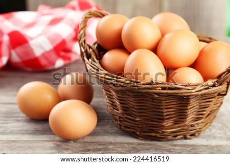 Chicken eggs in basket on grey wooden background - stock photo