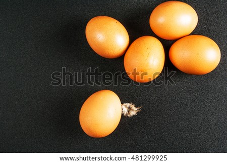 Chicken eggs on a black table. Top view, copy space