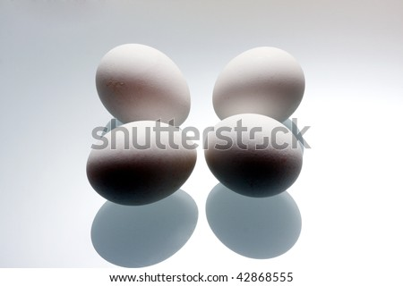 Chicken eggs on a glass table.