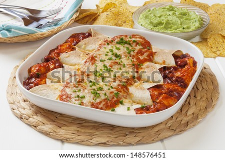 Chicken enchiladas with guacamole and corn chips. - stock photo