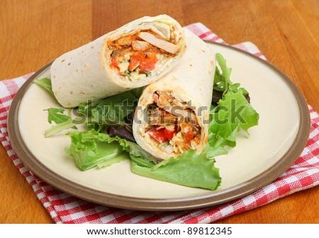 Chicken fajita wrap sandwich with lettuce leaves. - stock photo