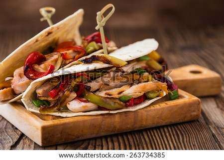 Chicken fajitas with grilled onions and bell peppers and serve with flour tortillas on rural wooden board - stock photo