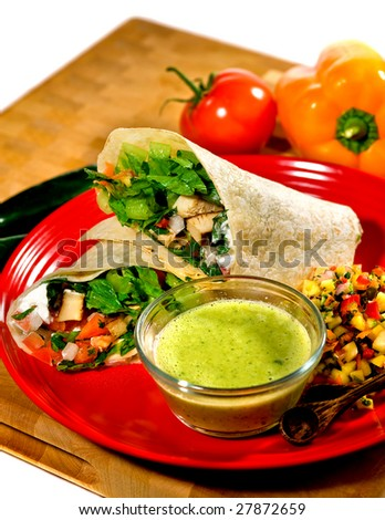 Chicken Fajitas with tomatoes, sauce and salad on plate. Ingredients in background. - stock photo