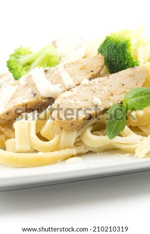 Chicken Fettuccini alfredo with fresh basil leaves and steamed fresh broccoli, delicious - stock photo