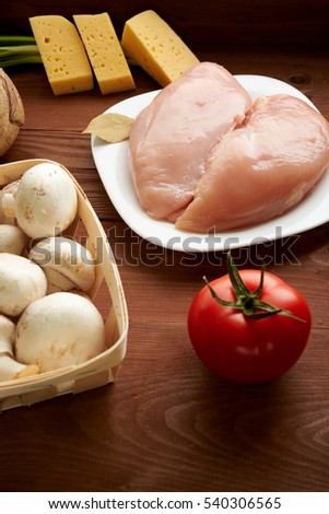 chicken fillet mushrooms, tomatoes on a wooden table
