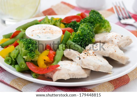 chicken fillet, steamed vegetables and yoghurt sauce, close-up, horizontal