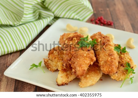 Chicken fingers breaded with cashew and coconut flakes garnish with parsley - stock photo