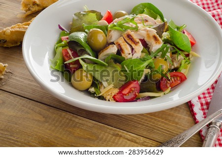 Chicken fresh salad on a rustic wooden table.