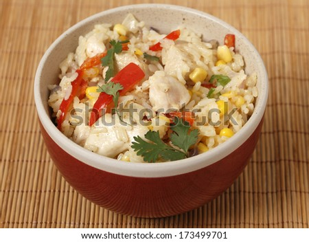 Chicken fried rice, containing capsicum, rice, garlic, egg, ginger and spices,  in a bowl