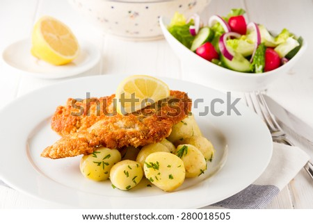 Chicken fried steak in wiener schnitzel style with spring potatoes, parsley, lemon and vegetable salad - stock photo