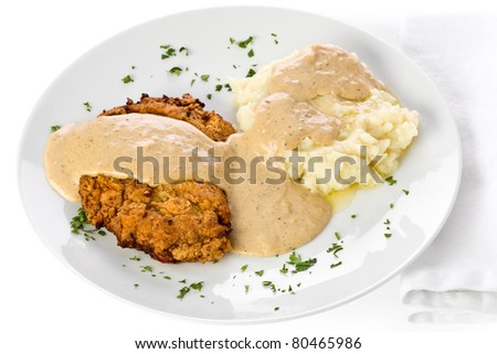 Chicken fried steak with mashed potato and gravy on a white plate. - stock photo