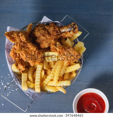 Chicken fries strips and legs with French fries in metal basket and bowl of ketchup sauce over blue wooden table with sea salt. Flat lay. Square image - stock photo