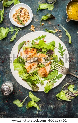Chicken green salad served on rustic table with pine nuts and oil dressing, top view. Healthy lifestyle and diet food concept. - stock photo
