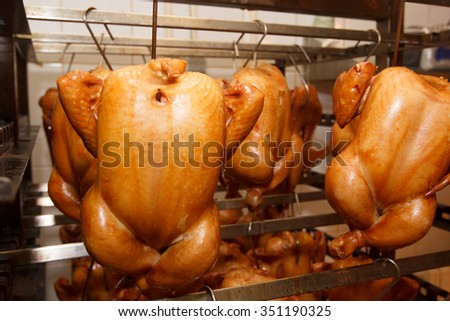 Chicken in a smoke chamber at the factory. The manufacture of smoked chicken. - stock photo