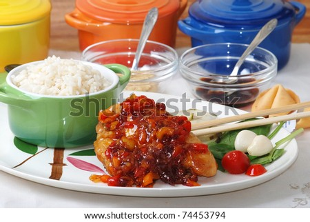Chicken in spicy orange glaze served on oriental platter with rice, soy sauce, hot mustard and eaten with chopsticks. - stock photo