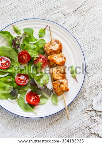 chicken kebab and fresh vegetable salad on a light wooden background - stock photo