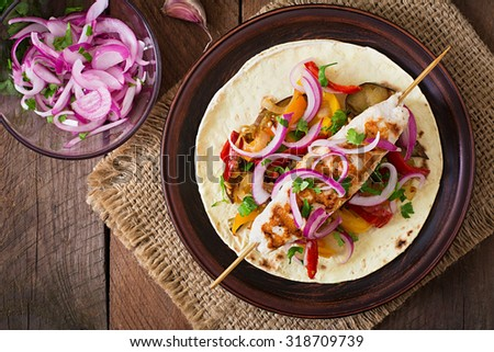 Chicken kebab with grilled vegetables and tortilla wrap. Top view - stock photo