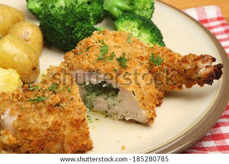 Chicken Kiev served with broccoli and new potatoes. - stock photo