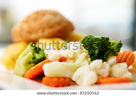 Chicken Kiev with cauliflower, carrot and broccoli.