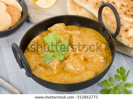 Chicken Korma - Chicken on a mildly spiced creamy sauce served with naan bread and poppadoms. Indian cuisine. - stock photo
