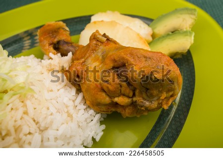 chicken leg served with white rice avocado and potato on a plate - stock photo
