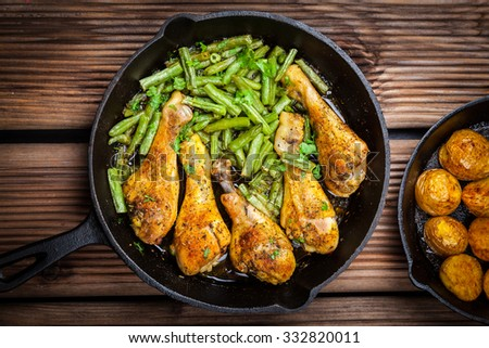 Chicken legs in pan with potatoes, green beans and salad - stock photo