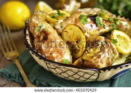 Chicken legs stewed in a cream lemon sauce on a rustic wooden background. - stock photo