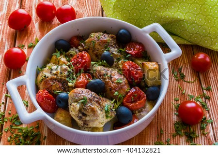 Chicken legs with potatoes, cherry tomatoes and black olives. White baking dish on wooden background.